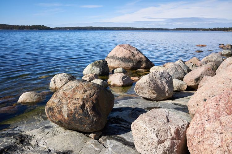 Rocks on shore by sea against sky