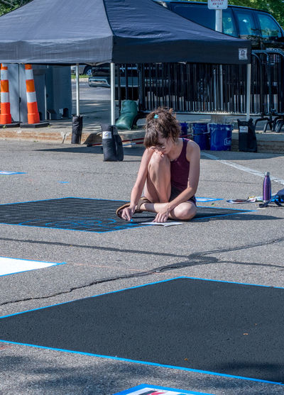 A young female artist works on a sketch on street asphalt, during a street art event in Michigan USA One Person Sitting Day Hairstyle Full Length Lifestyles Young Adult Nature Leisure Activity Girl Females Artist Darwing Event Editorial  Art Creativity St Joseph MI USA Chalk The Block Creativity Everywhere Idea Road Asphalt Pavement Street Art Street Artist