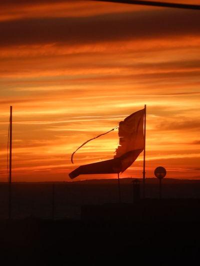 Silhouette flag against orange sky