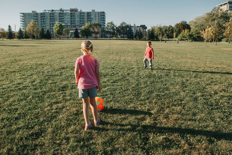 Girl and boy friends playing soccer football on playground grass field outside.