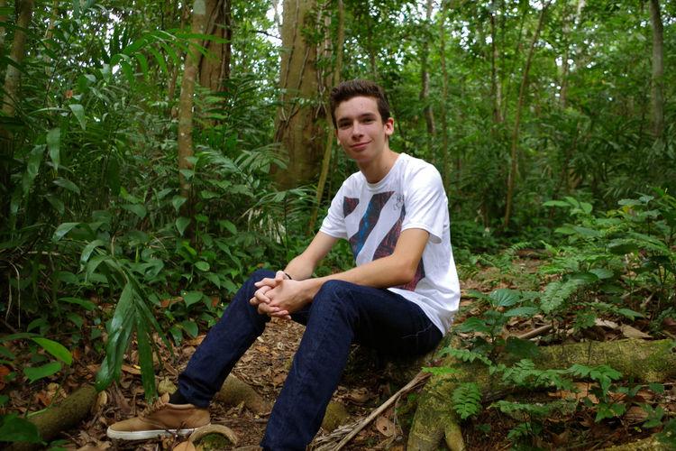 Portrait of boy sitting in forest