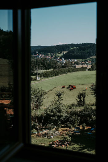 Scenic view of field against clear sky seen through window