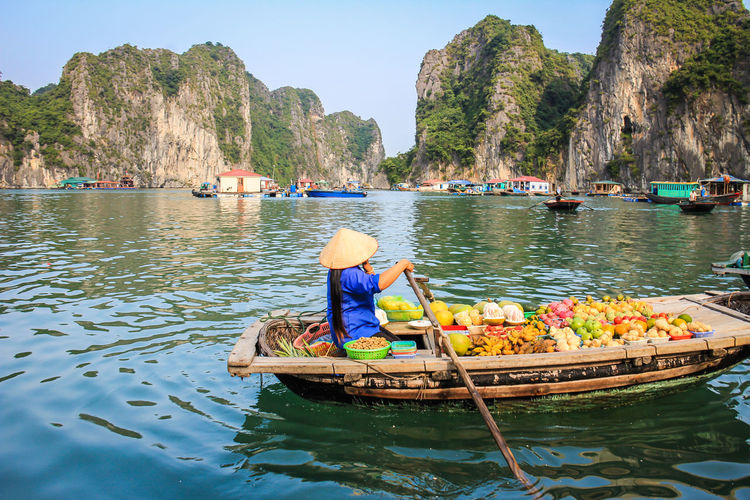 Vendor in Halong Bay Halong Bay Vietnam Halong Bay  Halong Bay Cruise Vietnam Water Nautical Vessel Transportation Mode Of Transportation Real People One Person Day Nature Hat Men Beauty In Nature Lifestyles Waterfront Sea Incidental People Mountain Three Quarter Length Women Outdoors