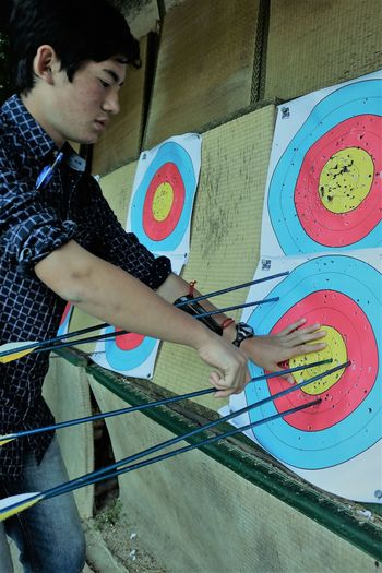Counting Up Target Adolescence  Archery Archery Bows Archery Range Archery Target Arrows Casual Clothing Hobbies Holding Human Hand Leisure Activity Lifestyles Males  Men One Person Side View Skill  Standing Target Practice Target Shooting Targets Teenager Three Quarter Length Young Adult