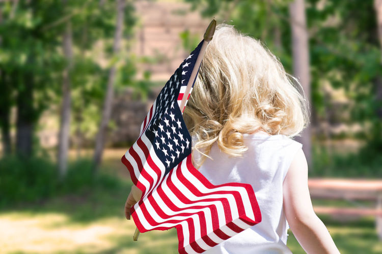 Rear view of girl holding american flag at fourth of july event