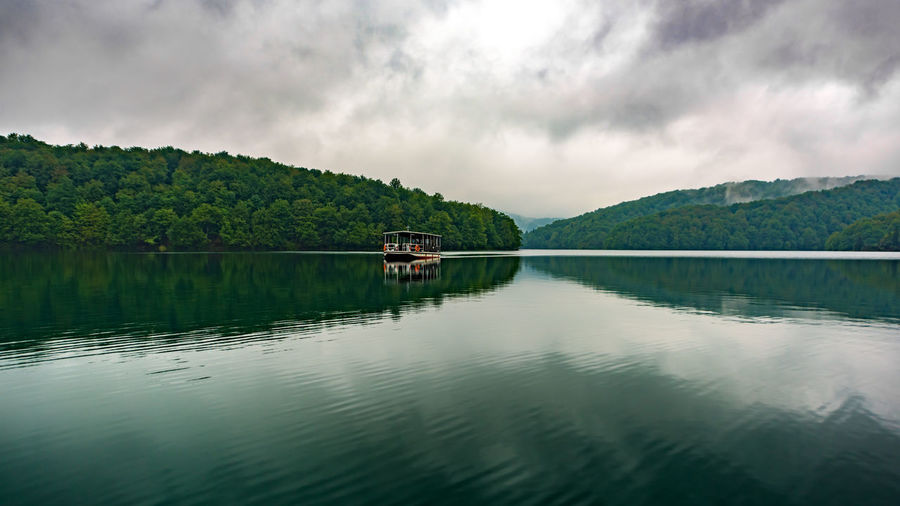 Beauty In Nature Boat Cloud Copy Space Idyllic Lake Landscape Nature No People Non-urban Scene Outdoors Plitvice Plitvice National Park Reflection Scenics The Great Outdoors - 2016 EyeEm Awards Tourism Tranquil Scene Water Feel The Journey We just had to catch the first boat over the lake, that rainy morning. Anything before the hoard of tourists arrive. On The Way
