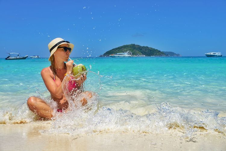 Woman drinking coconut water while sitting at beach against blue sky
