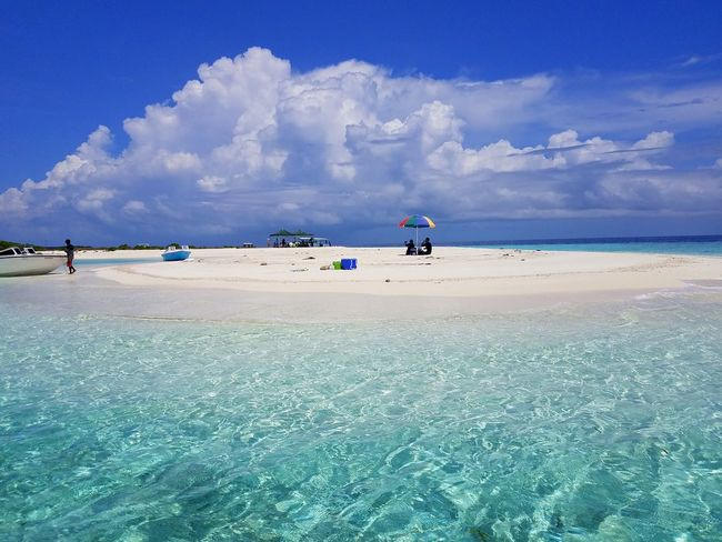 Beautiful crystal clear blue water near a white sandbank in Maldives Maldives Sandbank Blue Water Ocean Layer Shallow Deep Vacation Beach Sea Sky Sand Cloud - Sky Water Outdoors Blue Landscape Tranquility Full Length Scenics Low Tide Horizon Over Water Nature