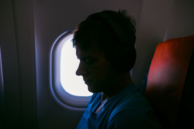 One Person Headshot Portrait Vehicle Interior Airplane Mode Of Transportation Transportation Travel Side View Window Young Adult Looking Contemplation Man Headphones Window Seat Lifestyles Clouds And Sky