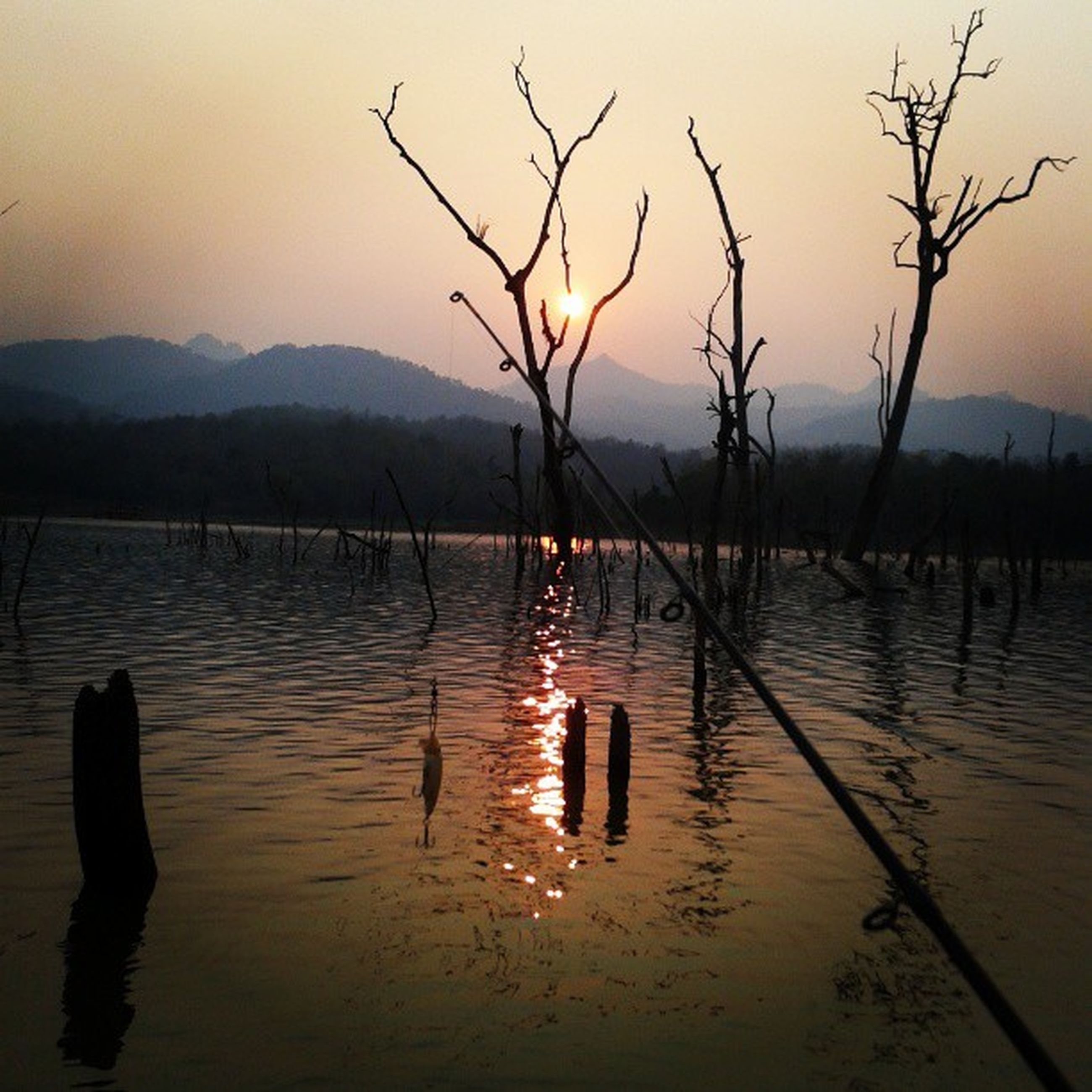 water, tranquil scene, tranquility, lake, sunset, reflection, scenics, silhouette, beauty in nature, bare tree, mountain, nature, waterfront, branch, sky, idyllic, mountain range, dusk, tree, rippled