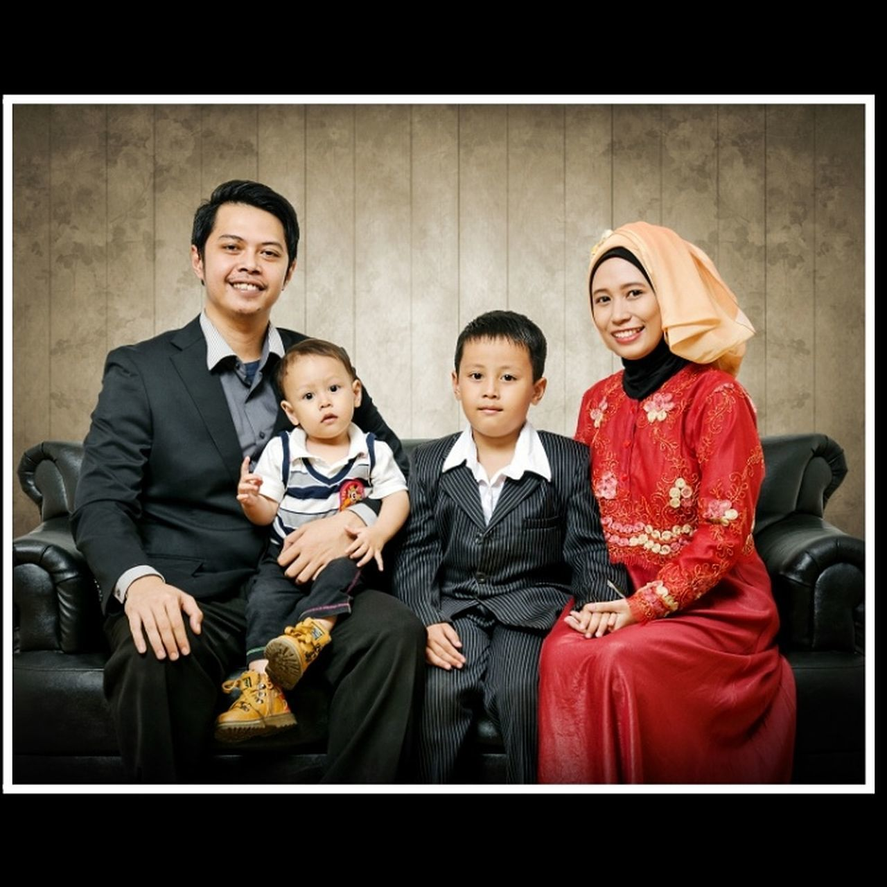 son, mother, looking at camera, father, portrait, daughter, men, togetherness, smiling, family, females, males, indoors, mature adult, women, mature women, boys, sitting, standing, group of people, happiness, well-dressed, adult, real people, child, people, young adult, day