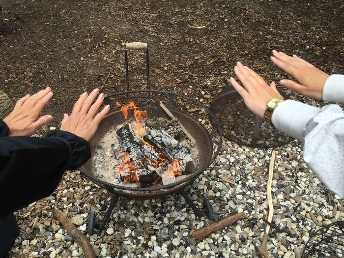 Cropped hands reaching towards fire pit on field