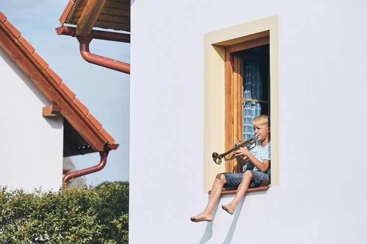 Little boy playing the trumpet in open window of the house. Artist Children Creativity Effort Freedom Home Little Boy Music Sitting Skill  Sound Boy Carefree Child Childhood House Musician Open Passion Player Playing Real People Talent Trumpet Window
