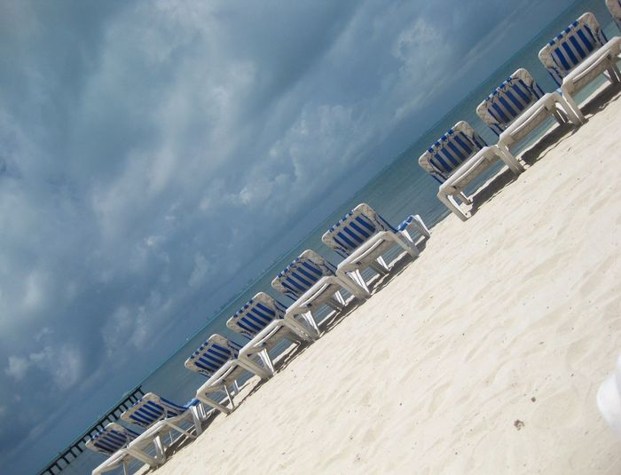 Tilt Image Of Deck Chairs At Beach Against Cloudy Sky