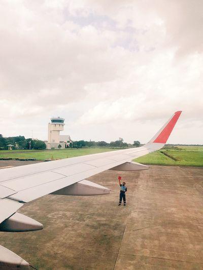 Man on airport runway against sky