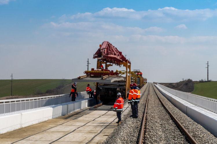People on railroad tracks against sky