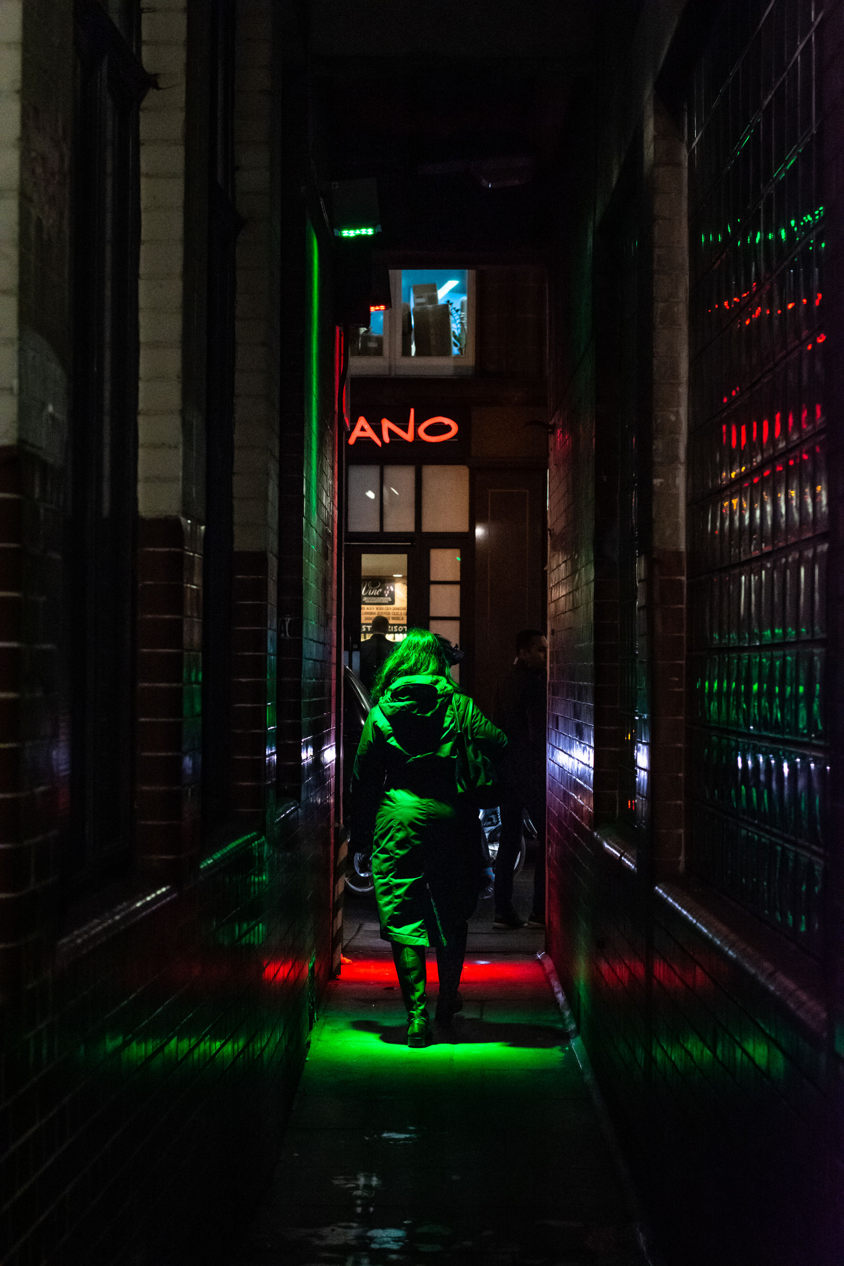 illuminated, architecture, one person, night, real people, full length, built structure, green color, building exterior, rear view, men, lifestyles, leisure activity, building, lighting equipment, walking, casual clothing, glowing, motion