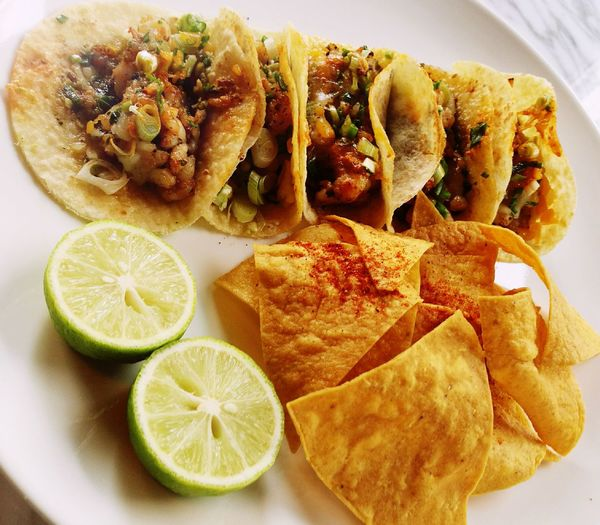 High angle view of tortilla chip and tacos in plate