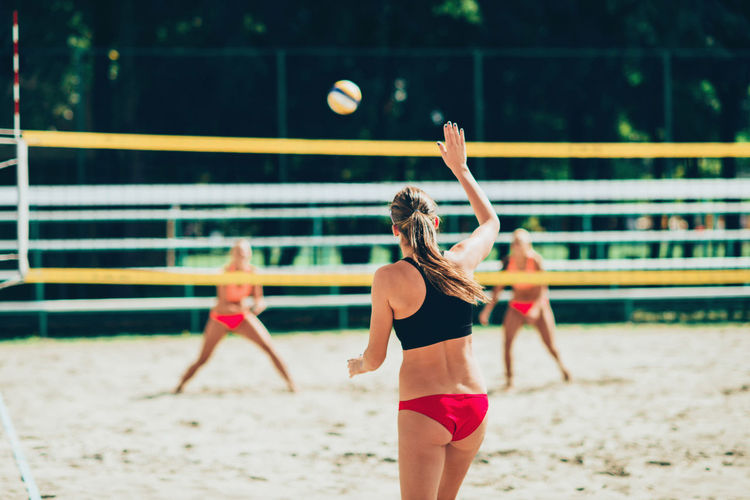 Rear view of woman playing beach volleyball