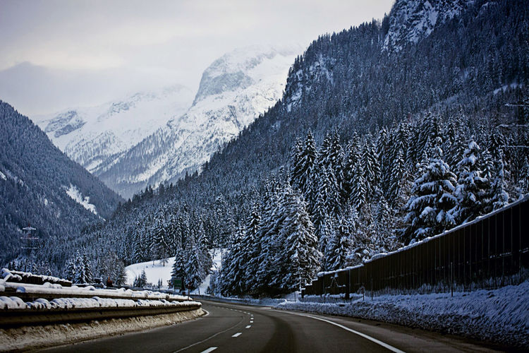 Road by snowcapped mountains during winter
