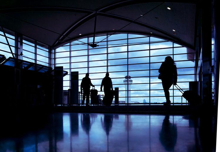 Silhouette people walking in airport