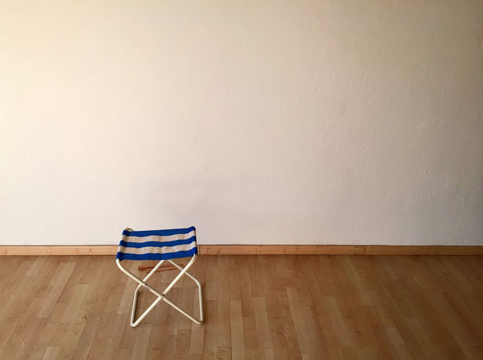 Seat On Hardwood Floor Against White Wall