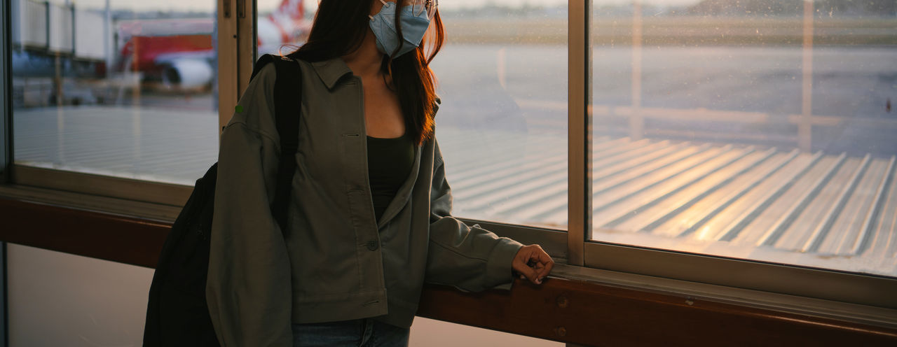 Midsection of woman standing by train window
