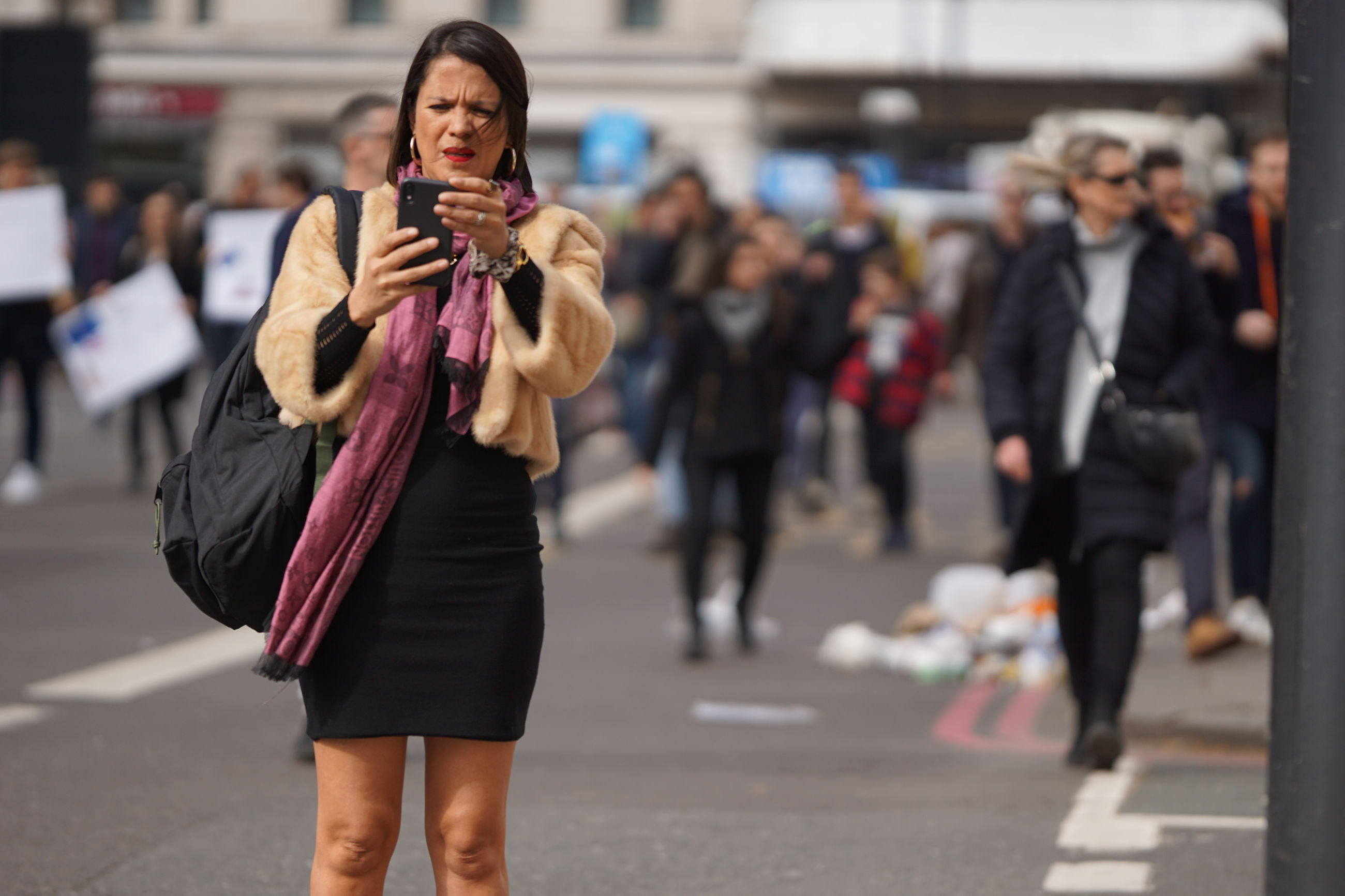 focus on foreground, real people, one person, city, adult, holding, lifestyles, standing, front view, incidental people, women, street, day, transportation, technology, leisure activity, young adult, clothing, communication, outdoors, hairstyle, scarf, warm clothing