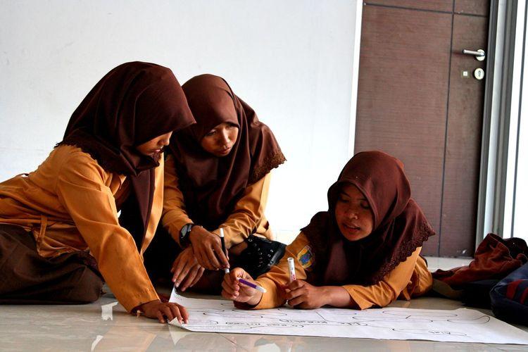 Muslim girls making project on floor