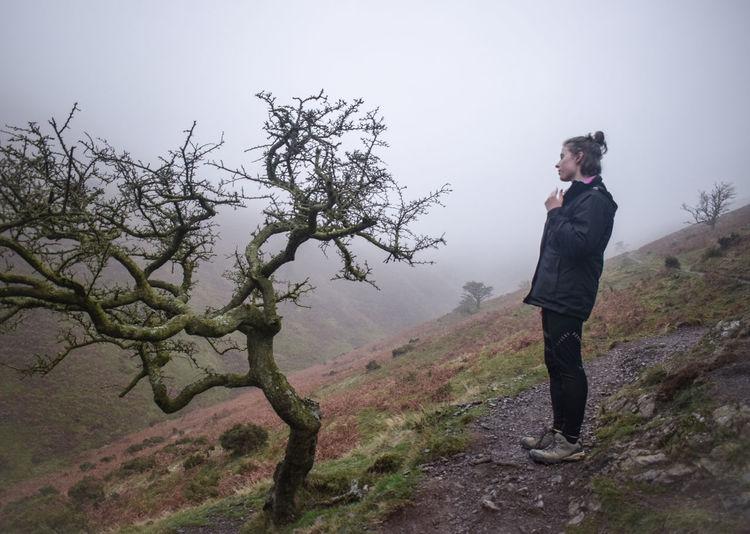 Full length of man standing by tree against sky