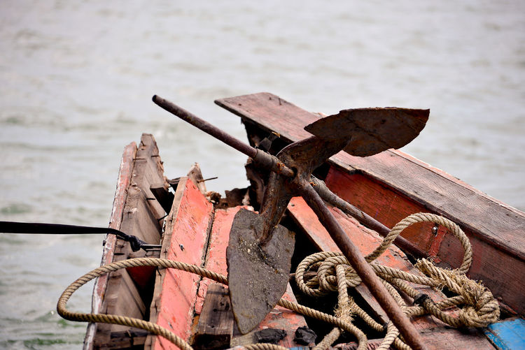 Close-up of abandoned boat against sea