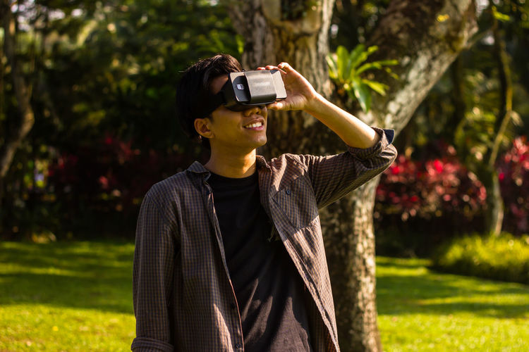Young man looking through virtual reality while standing at park