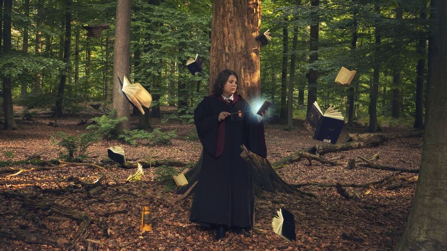 Teenage Girl Holding Magic Wand While Standing Amidst Books At Forest