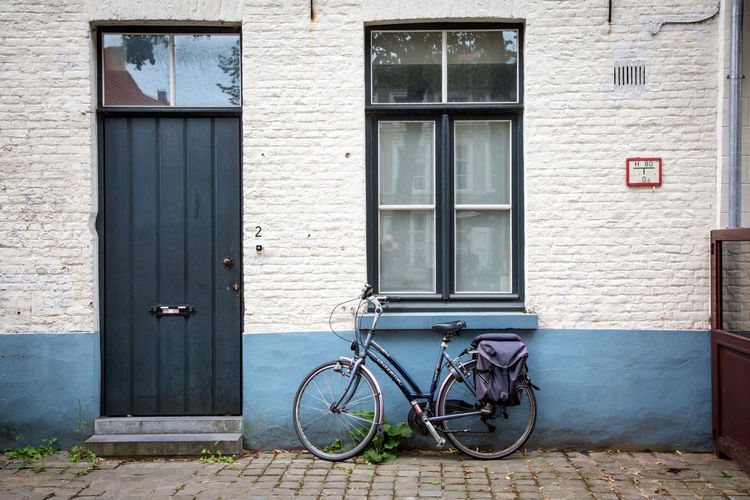 bicycle leaning against a building Architecture Bicycle Building Building Exterior Built Structure Closed Day Door Entrance House Land Vehicle Mode Of Transportation No People Outdoors Protection Residential District Safety Stationary Transportation Window