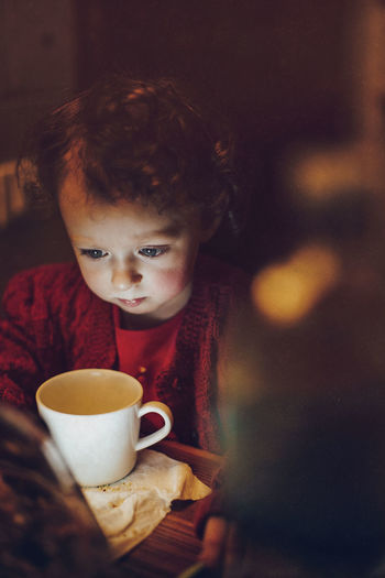 Cute girl looking at coffee in illuminated room