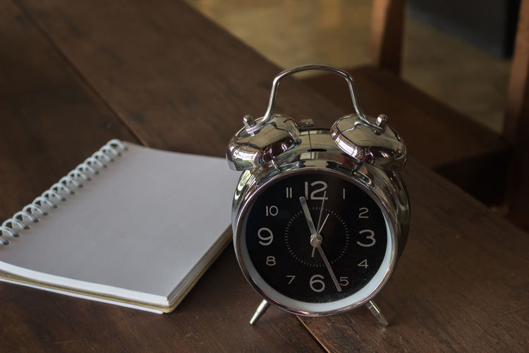 High angle view of alarm clock by diary on table