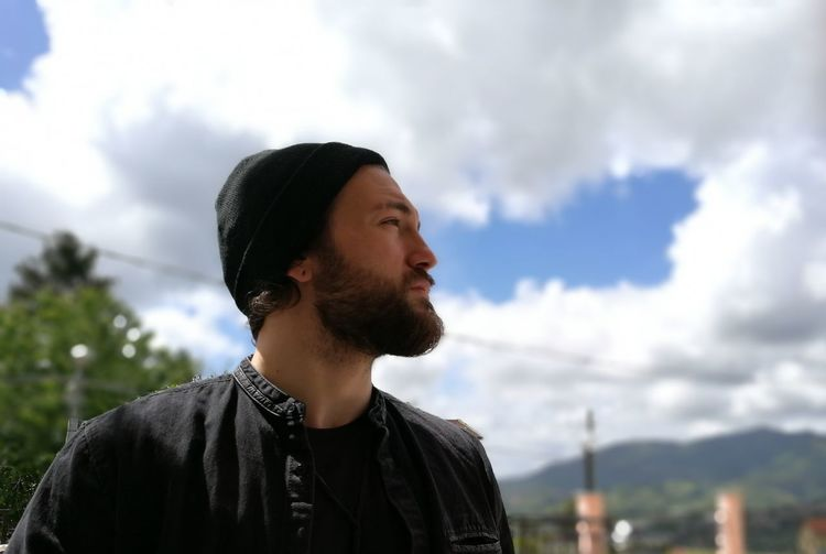 Confident bearded man looking away while standing against cloudy sky