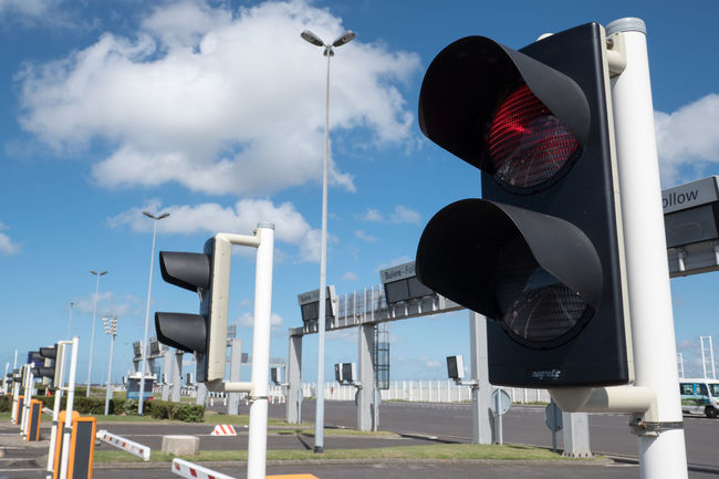 Traffic Lights at Eurotunnel Immigration Architecture Border Building Exterior Communication Day Eurotunnel Guidance Low Angle View No People Outdoors Road Sign Sky Stop Stoplight