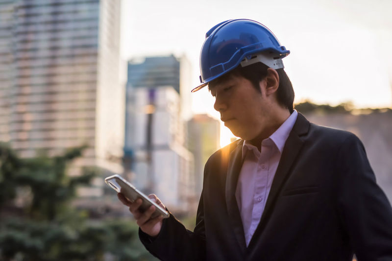 Man wearing hardhat using mobile phone outdoors