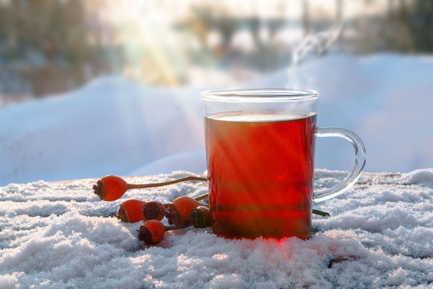 hot red tea from hibiscus and rose hip fruits outdoors in the snow with sunbeams, healthy warming drink for immunity protection against cold and flu, copy space Hot Red Remedy Tea Winter Antioxidant Cold Day Drink Flu Food And Drink Fruits Healthy Herbal Hibiscus Immune System Landscape Nature Outdoors Protection Rose Hips Snow Steam Sunbeams Vitamin
