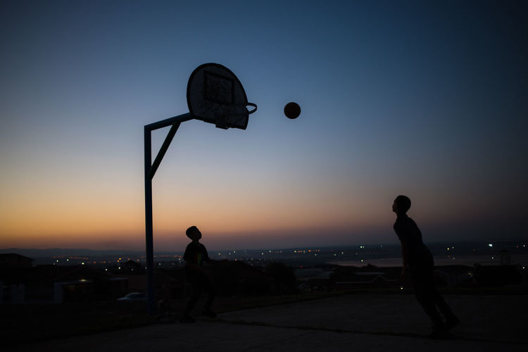 Silhouette people playing basketball against sky at sunset