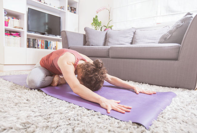 Young woman exercising yoga at home. Meditating Meditation Recreation  Yoga Active Lifestyle  Asana Fit Woman Fitness Healthy Lifestyle Indoors  Leisure Activity Recreational Pursuit Stretching Workout
