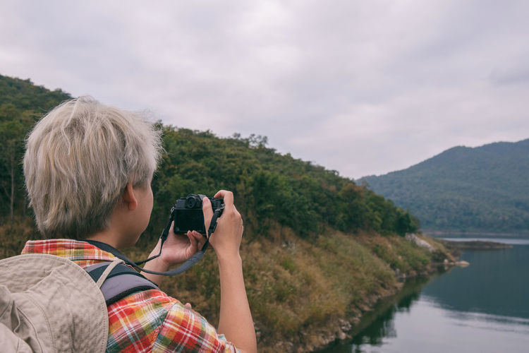 Man photographing lake and mountains against sky