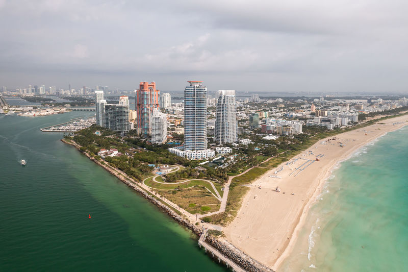 Aerial of south pointe high-rise buildings in miami beach with sandy shores lining turquoise waters.