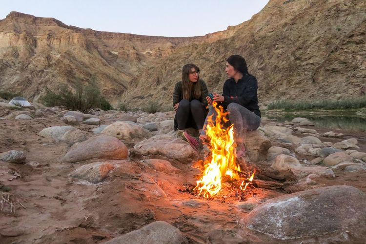 Two female friends sitting next to a campfire having a conversation Adventure Beauty In Nature Bonfire Campfire Chat Conversation Fire Flame Friends Mountain Mountain Range Nature Nature Outdoor Photography Outdoors Rock - Object Sand Scenics Sitting Talking Pictures Togetherness Two People Wilderness Women Young Women