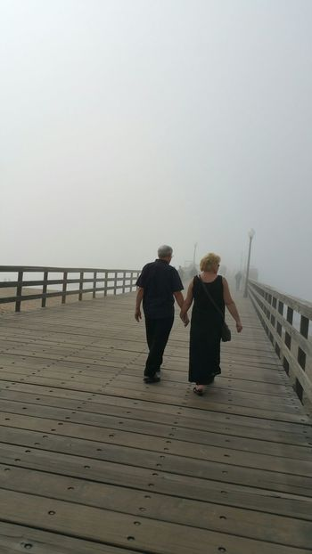 People Watching Couple Holding Hands pier Enjoying People Wandering Around Enjoying Life Peaceful Loving Foggy Pier Foggy Day Fog At Ocean Man And Woman Walking Into The Mist Soft White Space Letting Go Go With The Flow No Hurry Pier Stroll Pier Showcase: February Seal Beach California Surf's Up