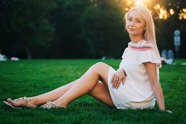 Portrait of beautiful woman sitting on grassy field at park