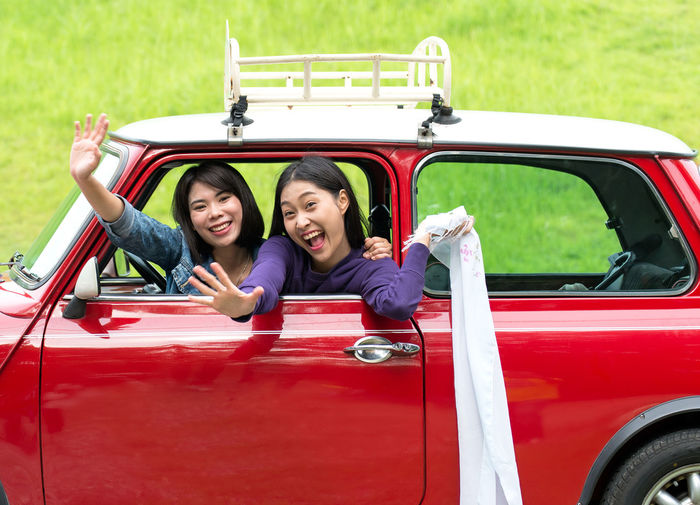 Portrait of smiling happy friends waving while sitting in car