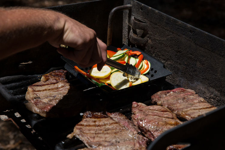 Cropped Image Of Man Preparing Meat On Barbeque Grill At Park