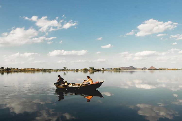 People sitting on boat in lake against sky